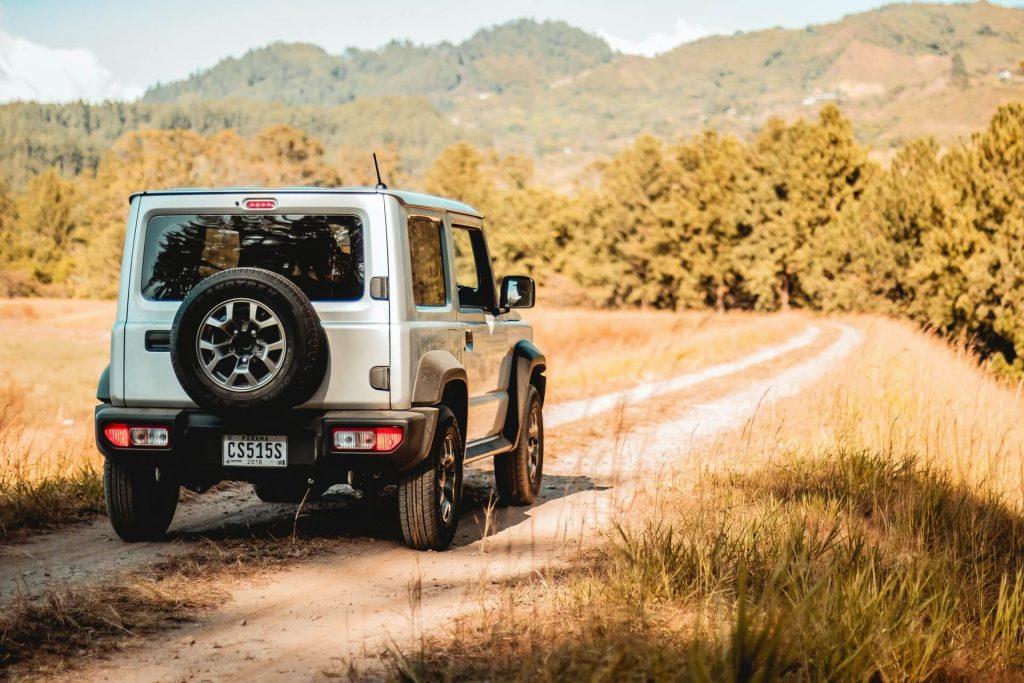 SUV driving along dirt trail