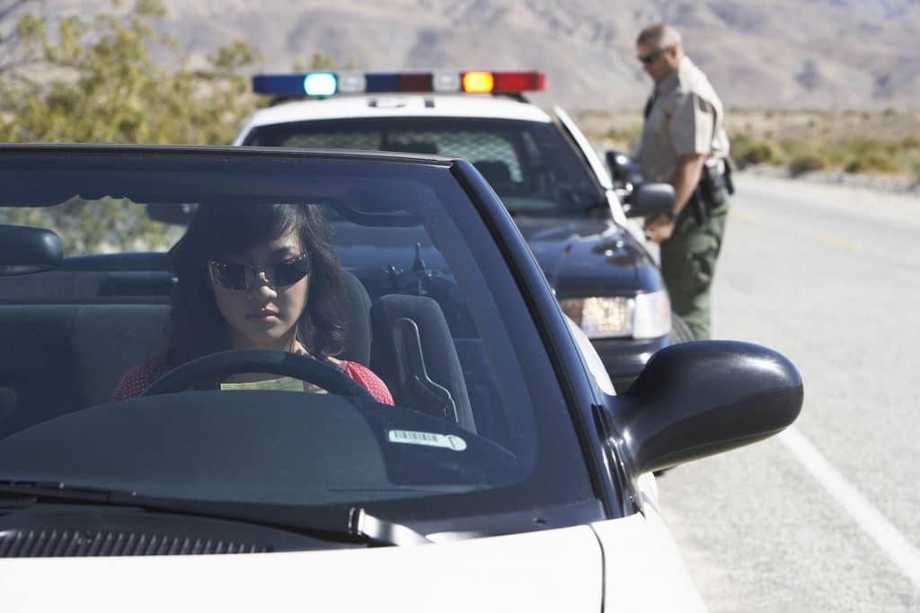 Police officer behind woman in convertible